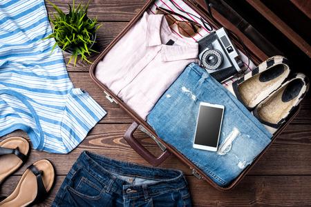 Photo pour Open suitcase with casual female clothes on wooden table - image libre de droit