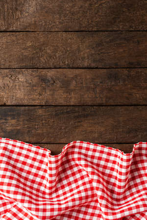Photo pour Red checkered tablecloth on wooden background with copyspace - image libre de droit