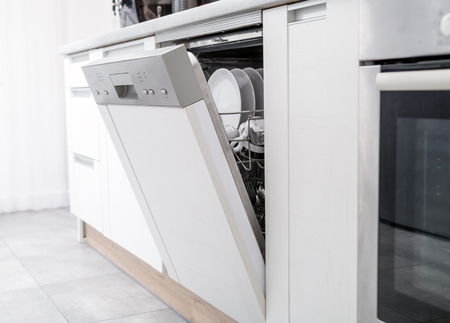 Photo pour Open dishwasher with clean dishes in the white kitchen - image libre de droit