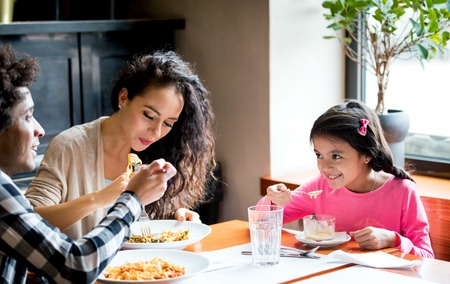 Photo pour Happy african american family eating lunch together at restaurant and having fun - image libre de droit