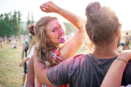 Photo for Beautiful young woman covered in colorful powder standing with friends at holi festival - Royalty Free Image
