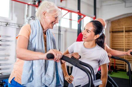 Photo pour Senior woman biking at the gym with personal trainer - image libre de droit