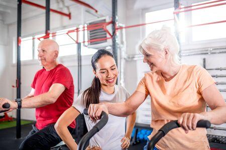 Photo pour Senior couple biking at the gym with personal trainer - image libre de droit