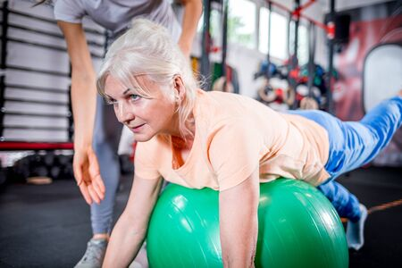 Photo pour Senior woman with trainer doing rehab using pilates ball in the rehabilitation center - image libre de droit