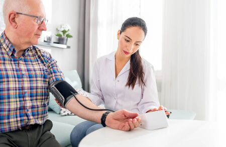 Photo pour Nurse visiting senior male at home doing blood pressure measurement - image libre de droit
