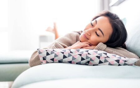 Foto per Happy asian girl lying on sofa with pillow at home - Immagine Royalty Free