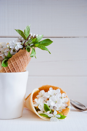 Photo pour Fresh flowers in ice cream cone still life on a light wooden background - image libre de droit