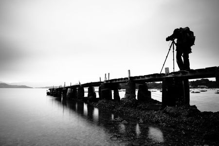 a man taking photo on the wooden pier, black and white