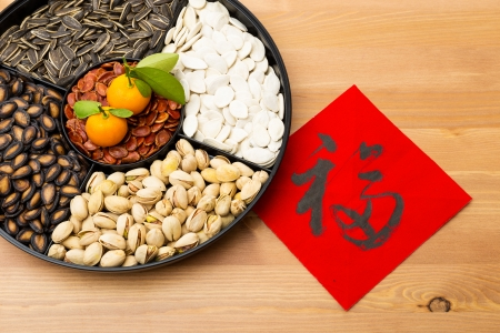 Traditional Lunar new year snack tray and chinese calligraphy, meaning for blessing good luck