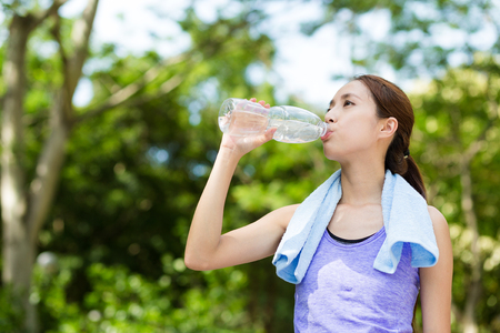 Foto de Athlete woman drinking water from a plastic bottle - Imagen libre de derechos