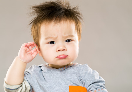 Photo for Confused baby boy hand touch ear - Royalty Free Image