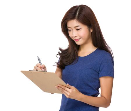 Woman take note on file board