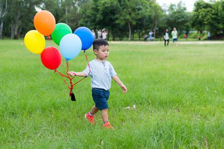 Little boy holding a bunch of balloon