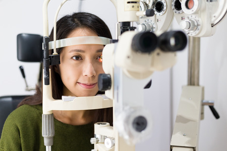 Photo for Woman checking vision with equipment - Royalty Free Image