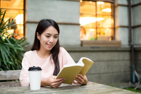 Foto de Woman reading boo at outdoor cafe - Imagen libre de derechos