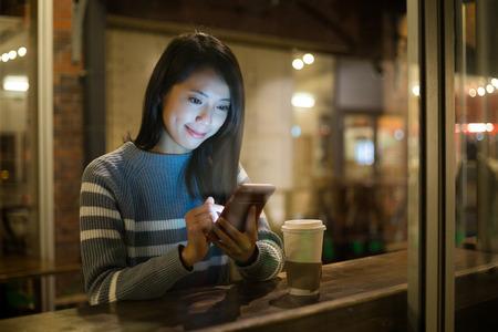 Photo pour Woman using cellphone at coffee shop - image libre de droit