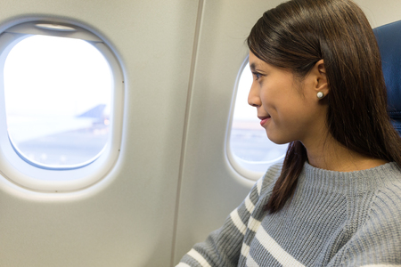 Woman looking out of the window in airplane