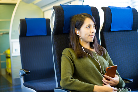 Woman listen to music on mobile phone inside train compartment