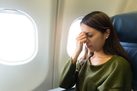 Photo pour Fear of flying woman in plane airsick with stress headache - image libre de droit