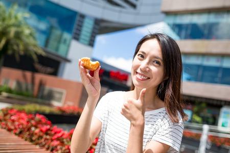 Woman having egg tart in Hong Kong