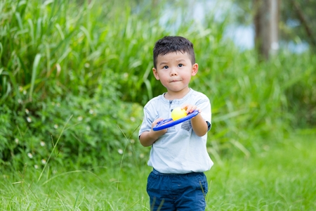 Asian little boy playing tennis at park