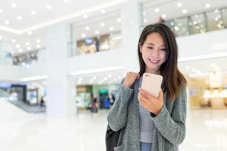 Woman use of cellphone in shopping plaza