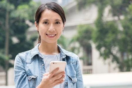Photo pour Woman use of mobile phone in Hong Kong  - image libre de droit