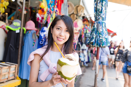 Young woman shopping at street and enjoy coconut juicy