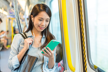 Photo pour Woman listen to song on phone and taking the train in Hong Kong - image libre de droit