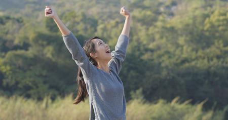 Foto de Excited woman raising hand up - Imagen libre de derechos