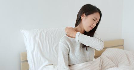 Foto de Woman feeling shoulder pain on bed - Imagen libre de derechos