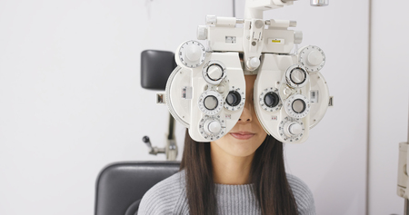 Foto de Asian Woman doing eye test in clinic - Imagen libre de derechos