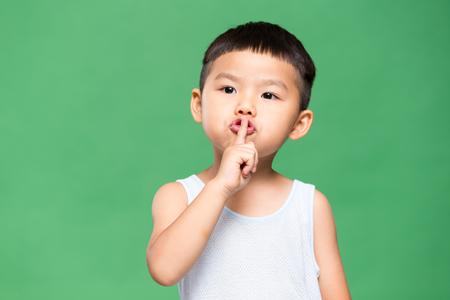 Photo pour Little kid putting a finger on his lips - image libre de droit