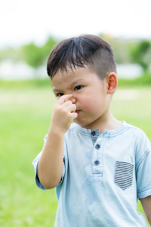 Little boy with hand pinch on his nose