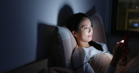 Photo pour Woman use of mobile phone on bed at night - image libre de droit