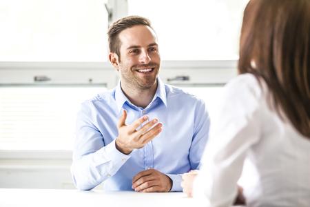 Photo pour Young businessman discussing with female colleague in office - image libre de droit