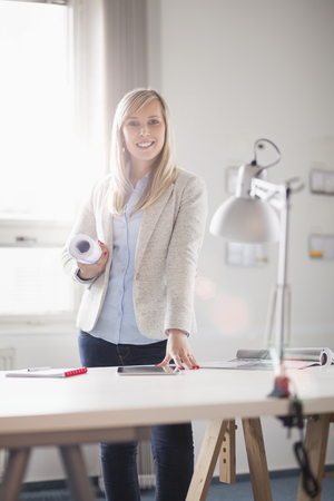 Portrait of confident young female architect standing at table in office