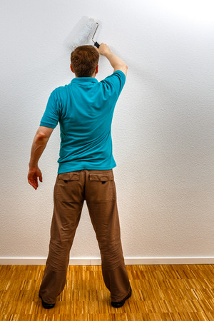 Man paints wall in white, vertical format
