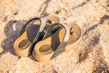 Photo pour sandals stand on the sea sand on a hot summer day - image libre de droit
