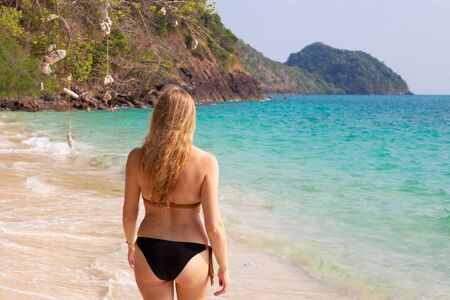 Photo pour a woman with long hair enters the clear blue sea, real people - image libre de droit