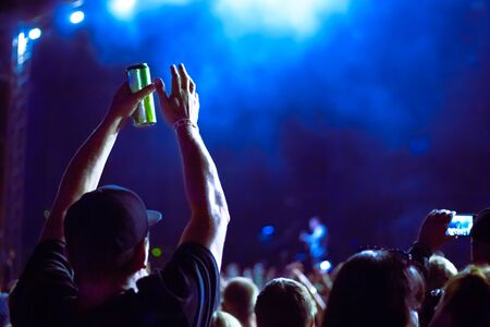 Photo pour A man holds a can of beer and claps his hands at a music festival - image libre de droit