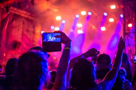 Photo pour a group of youth dancing with their hands up and taking videos and photos on the phone in a nightclub,blurred background - image libre de droit