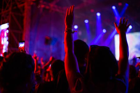 Photo pour woman raised her hands up at a concert, dancing, lit by bright light at the festival at night - image libre de droit