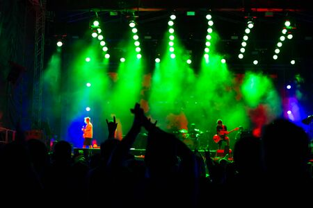 Photo pour people at a music concert dance and applaud, street festival at night, entertainment and leisure activities for youth, blurred background - image libre de droit