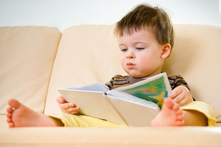 Photo for Little boy reading book on sofa  - Royalty Free Image