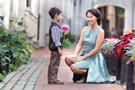 Photo pour Little boy giving flower to his mom on mother s day - image libre de droit