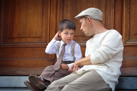 Happy father and son talking and having rest outdoors in city  in city on beautiful summer day