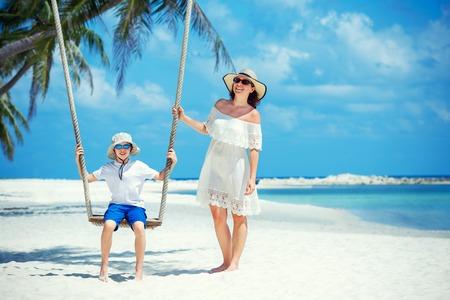 Foto für Young beautiful woman swinging her son on a tropical beach, Koh Phangan island. Thailand, Asia - Lizenzfreies Bild