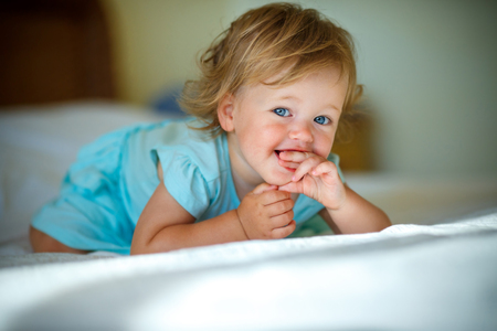 Photo pour Lovely blonde toddler girl lying at home or kindergarten on a bed - image libre de droit