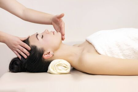 Photo pour Massage and body care. Spa massage of the head and neck of a woman. Woman having massage in the spa for a beautiful girl - image libre de droit